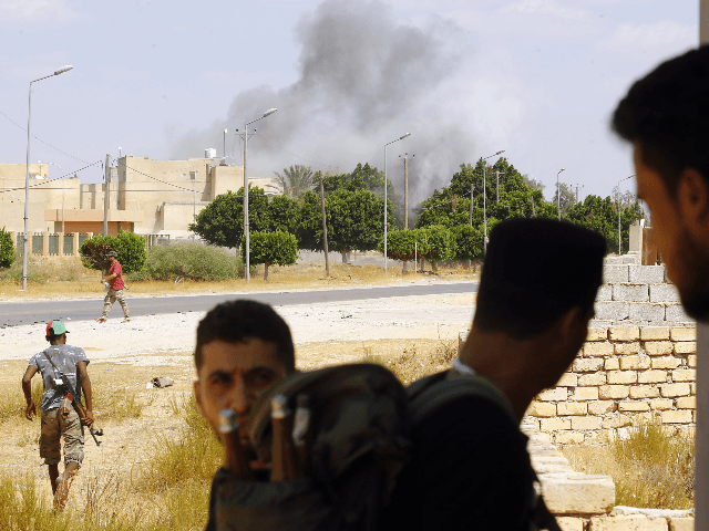 A plume of smoke rises above buildings as fighters loyal to the internationally-recognised Government of National Accord (GNA) gather during clashes with forces loyal to strongman Khalifa Haftar, in Espiaa, about 40 kilometers (25 miles) south of the Libyan capital Tripoli on August 21, 2019. (Photo by Mahmud TURKIA / …