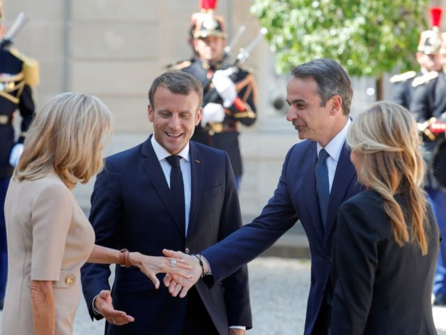 French President Emmanuel Macron (C-L) and his wife Brigitte Macron (L) welcome Greek Prime Minister Kyriakos Mitsotakis (C-R) and his partner Mareva Grabowski as they arrive for a meeting at the Elysee Palace in Paris on August 22, 2019. (Photo by GEOFFROY VAN DER HASSELT / AFP) (Photo credit should …