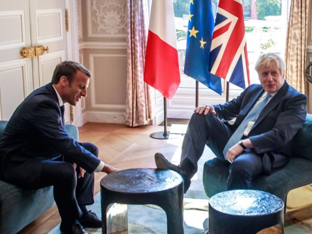 TOPSHOT - Britain's Prime Minister Boris Johnson (R) places his foot on the table during a meeting with French President Emmanuel Macron (L) at the Elysee Palace in Paris, France, on August 22, 2019. - British Prime Minister is visiting Paris, a day after Berlin offered a glimmer of hope …