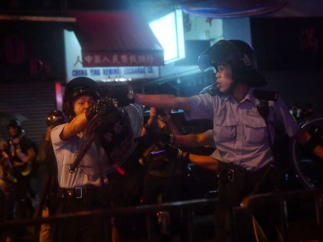 TOPSHOT - Police officers point their guns at protesters in Tseun Wan in Hong Kong on August 25, 2019 in the latest opposition protests to a planned extradition law that has since morphed into a wider call for democratic rights in the semi-autonomous city. - A Hong Kong police officer …