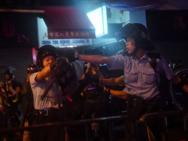 Police officers point their guns at protesters in Tseun Wan in Hong Kong on August 25, 2019. (Photo by Lillian Suwanrumpha/AFP/Getty Images)