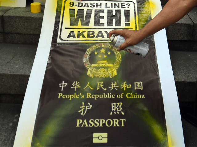 Philippine legislator Walden Bello (R-arm in frame) sprays paint on a placard featuring a mock cover of a Chinese passport during a demonstration in front of the Chinese consular office in Manila on November 29, 2012 against reports that Chinese passports contain a map showing most of the China South …