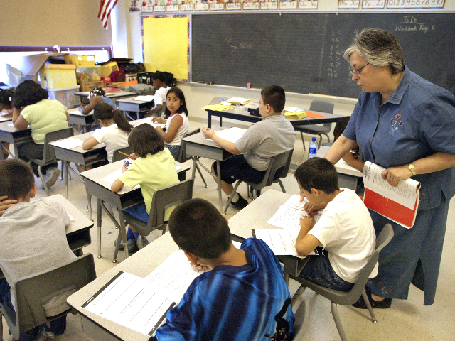 Teacher Arlene Lebowitz assists a student in her third-grade class during summer school July 2, 2003 in Chicago, Illinois. A record number of students are expected at summer school due to a strong showing for a new voluntary program for mid-tier students and strict application of non-ITBS (Iowa Tests of …