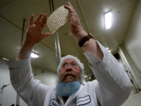 Rabbi Yaakov Horowitz examines the holes in a sheet of baked matzo from the matzo production line at the Manischewitz manufacturing facility on February 4, 2014 in Newark, New Jersey. Under strict rabbinical supervision at all times and in all stages of production, over 1 million sheets of matzo are …