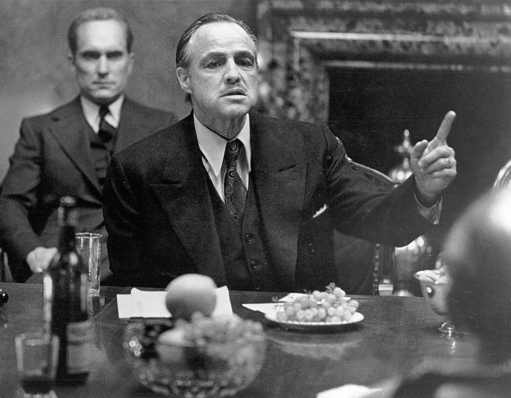 American actor Marlon Brando (1924 - 2004), in character as mob kingpin Don Vito Corleone, gestures as he sits at a table as colleague and compatriot Robert Duvall, as Tommy Hagen, sits behind him in a scene from the gangster film 'The Godfather,' directed by Francis Ford Coppola, 1972. (Photo by Paramount Studios courtesy of Getty Images)