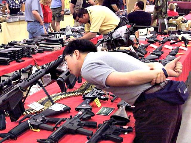 visitor to the Great Western Show checks out an assortment of assault rifles at the One-Eyed-Jacks, Inc., booth at the Las Vegas Convention Center 28 April 2000 in Las Vegas, Nevada. The show, which runs through 30 April 20000, recently moved to Las Vegas from California. AFP PHOTO/John GURZINSKI (credit: …