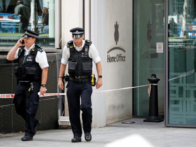 British Police officers leave the entrance to Britain's Home Office in central London on August 15, 2019, following a stabbing incident. - A man was taken to hospital after being stabbed Thursday outside Britain's Home Office interior ministry in London. One man was arrested at the scene on suspicion of …