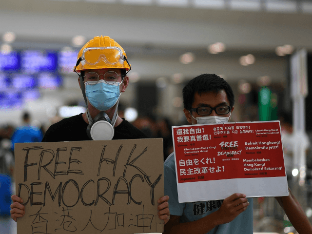 Pro-Democracy protesters gather against the controversial extradition bill at Hong Kong's international airport on August 11, 2019. - Empty hotel rooms, struggling shops and even disruption at Disneyland: months of protests in Hong Kong have taken a major toll on the city's economy, with no end in sight. (Photo by …
