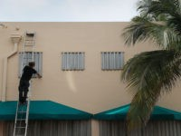 MIAMI BEACH, FLORIDA - AUGUST 30: Endre Eles places a hurricane shutter over a window as he helps prepare a business for the possible arrival of Hurricane Dorian on August 30, 2019 in Miami Beach, Florida. Dorian could be a Category 4 storm when it makes landfall Monday somewhere along …