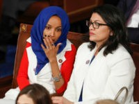 Rep. Ilhan Omar, D-Minn., left, joined at right by Rep. Rashida Tlaib, D-Mich., listens to President Donald Trump's State of the Union speech, at the Capitol in Washington, Tuesday, Feb. 5, 2019. (AP Photo/J. Scott Applewhite)