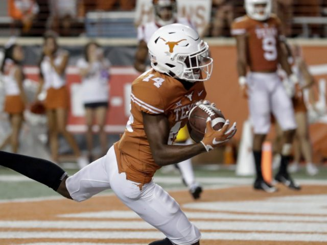 AUSTIN, TX - SEPTEMBER 15: Joshua Moore #14 of the Texas Longhorns catches a pass for a touchdown in the third quarter defended by Ajene Harris #27 of the USC Trojans at Darrell K Royal-Texas Memorial Stadium on September 15, 2018 in Austin, Texas. (Photo by Tim Warner/Getty Images)