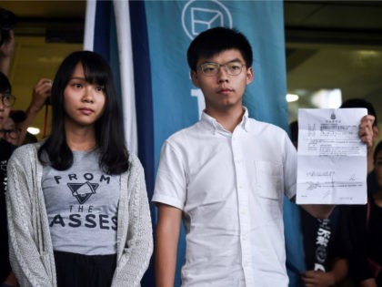 Pro-democracy activists Agnes Chow (L) and Joshua Wong (R) show the charges to the press after they were released on bail at the Eastern Magistrates Courts in Hong Kong on August 30, 2019. - Prominent democracy activists including a lawmaker were arrested on August 30 in a dragnet across Hong …