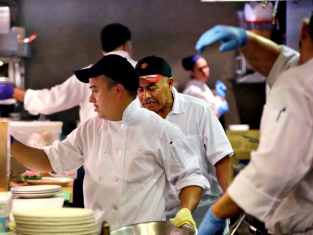 In this photo taken Monday, July 27, 2015, Arturo Ramirez, left, and other workers crowd the kitchen at an Ivar's restaurant in Seattle. After Seattle's new minimum wage law took effect last April 1, Ivar's Seafood Restaurants announced that it was jacking up its prices by about 21 percent, eliminating …