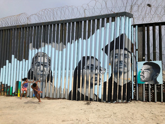 Children play in front of a new mural on the Mexican side of a border wall in Tijuana, Mexico Friday, Aug. 9, 2019. The mural shows faces of people deported from the U.S. with barcodes that activate first-person narratives on visitors' phones. Lizbeth De La Cruz Santana conceived the interactive …
