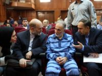 Former Tehran mayor Mohammad Ali Najafi (2nd-R), accused of shooting his second wife, speaks with his lawyer ahead of his trial at Iran's criminal court on July 13, 2019. - The high-profile trial opened today of a former Tehran mayor charged with murdering his wife, Iranian media reported. The charge …