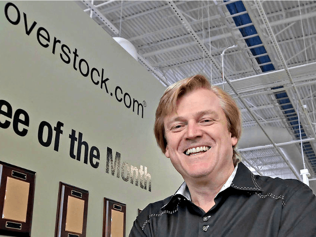 This March 25, 2010, file photo, chairman and CEO of OverStock.com Patrick Byrne poses for a picture by the employee of the month wall at the warehouse of Overstock.com outside of Salt Lake City, Utah. AP