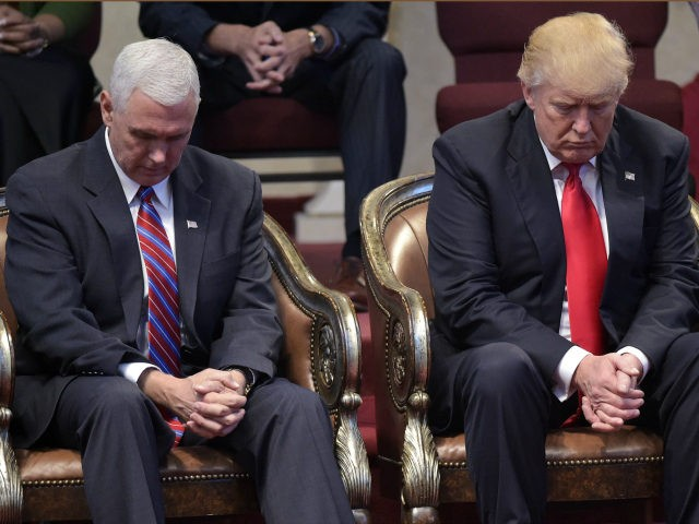 Republican presidential nominee Donald Trump (R) and running mate Mike Pence bow their heads in prayer during the Midwest Vision and Values Pastors and Leadership Conference at the New Spirit Revival Center in Cleveland Heights, Ohio on September 21, 2016. / AFP PHOTO / MANDEL NGAN (Photo credit should read …