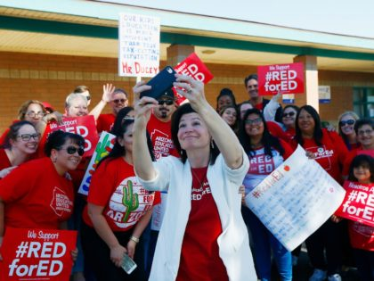 Teachers pose for a photograph with NEA President Lily Eskelsen García, middle, after the #RedForEd Walkout, March and Rally held a news conference at the Esperanza Elementary School in Isaac School District Wednesday, April 25, 2018, in Phoenix. Arizona teachers are due to go on strike Thursday. (AP Photo/Ross D. …