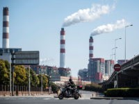 A man rides his scooter near the Shanghai Waigaoqiao Power Generator Company coal power plant in Shanghai on March 6, 2017. / AFP PHOTO / Johannes EISELE (Photo credit should read JOHANNES EISELE/AFP/Getty Images)