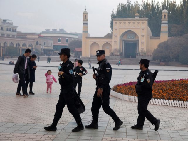 """FILE - In this Nov. 4, 2017 file photo, Uighur security personnel patrol near the Id Kah Mosque in Kashgar in western China's Xinjiang region. China's northwestern region of Xinjiang has revised legislation to allow the detention of suspected extremists in """"education and training centers."""" The revisions come amid rising …"""