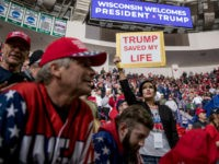 "A woman in the audience holds a sign that reads ""Trump Saved My Life"" as she waits for President Donald Trump to take the stage at a rally at Resch Center Complex in Green Bay, Wis., Saturday, April 27, 2019. (AP Photo/Andrew Harnik)"