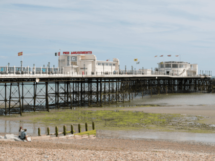 WORTHING, UNITED KINGDOM - JULY 04: People sit beside Worthing Pier, the destination of a convoy of around 90 London taxis that have brought approximately 200 WWII veterans for a day at the seaside on July 4, 2017 in Worthing, England. Following an annual tradition that began in 1948, London …