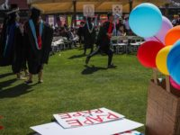 Students walk by a sign that lays on the ground that was made in support of a Stanford rape victim, during graduation ceremonies at Stanford University, in Palo Alto, California, on June 12, 2016. Stanford students are protesting the universitys handling of rape cases alledging that the campus keeps secret …