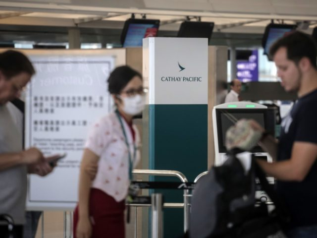 "A staff member helps passengers in the Cathay Pacific Airways check-in area at Hong Kong's International Airport on August 10, 2019. - Hong Kong pro-democracy activists kept up the pressure on authorities with a colourful ""family rally"" and a sit-in at the city's airport, as protests enter a third month. …"