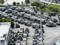 This Friday, Aug. 16, 2019, photo shows armored vehicles and troop trucks are parked outside Shenzhen Bay Stadium in Shenzhen, China. Members of China's paramilitary People's Armed Police marched and practiced crowd control tactics at a sports complex in Shenzhen across from Hong Kong on Friday, in what some interpreted …