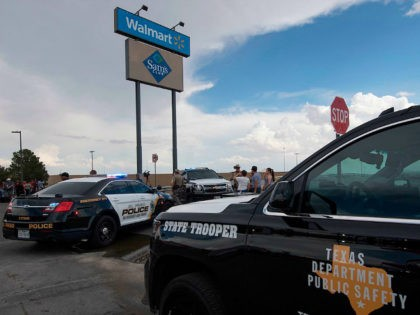 Police and state troopers keep watch outside the Cielo Vista Mall Wal-Mart (background) where a shooting left 20 people dead in El Paso, Texas, on August 4, 2019. - A shooting at a Walmart store in Texas left multiple people dead. At least one suspect was taken into custody after …