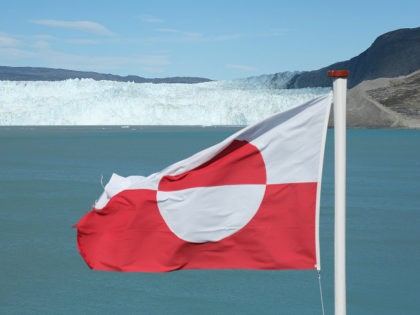 EQIP SERMIA, GREENLAND - JULY 31: A Greenlandic flag flies near the Eqip Sermia glacier, also called the Eqi Glacier, on July 31, 2019 at Eqip Sermia, Greenland. As the Earth's climate warms summers have become longer in the region, allowing fishermen a wider period to fish from boats on …