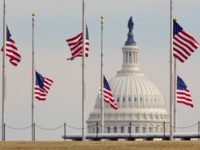 US flags fly at half-staff as tourists take photos at the Washington Monument with the US Captiol seen behind January 10, 2011 in Washington, DC in honor of the six people killed in the shooting in Tucson, Arizona, that also severely wounded Arizona Representative Gabrielle Giffords. AFP Photo/Nicholas Kamm (Photo …