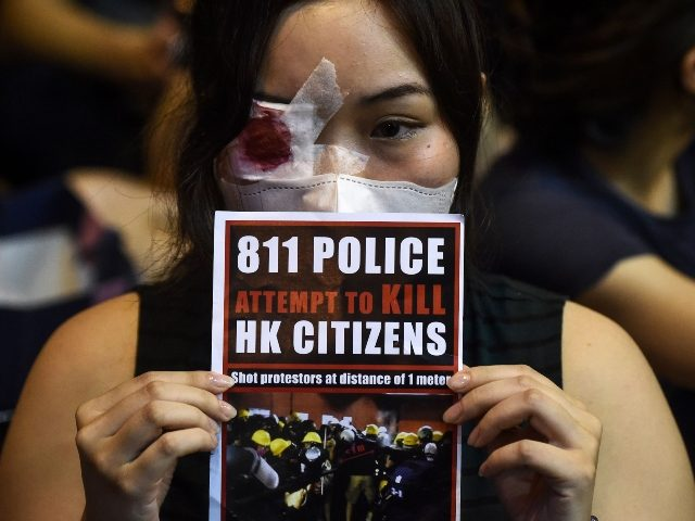 An anti-extradition bill protester holds a sign against police brutality during a gathering at Chater House Garden in Hong Kong on August 16, 2019. - Hong Kong's pro-democracy movement faces a major test this weekend as it tries to muster another huge crowd following criticism over a recent violent airport …