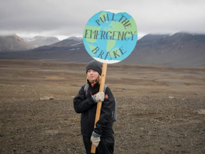 """TOPSHOT - An Icelandic girl poses for a photo with a """"Pull the emergency brake"""" sign near to where a monument was unveiled at the site of Okjokull, Iceland's first glacier lost to climate change in the west of Iceland on August 18, 2019. (Photo by Jeremie RICHARD / AFP) …"""