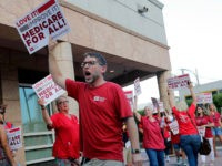People with National Nurses United march in support of medicare for all, outside of the Knight Concert Hall at the Adrienne Arsht Center for the Performing Arts of Miami-Dade County, where a Democratic presidential debate is taking place, Wednesday, June 26, 2019, in Miami. (AP Photo/Lynne Sladky)