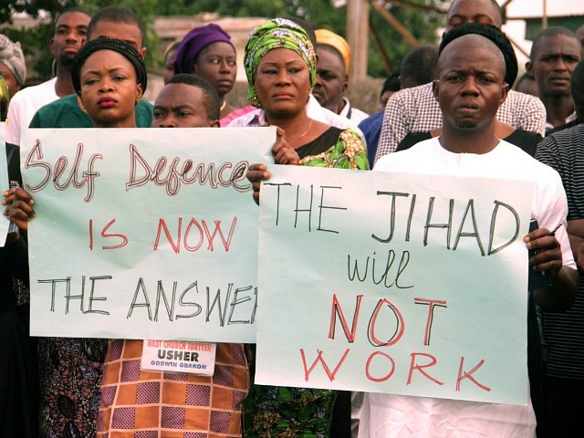 "Church members carry placards reading ""self defence is now the answer"" ""the jihad will not work"", as they take part in a protest against the killing of people by suspected herdsmen in Makurdi, north-central Nigeria, on April 29, 2018. - On April 24, 2018, at least 18 people, including two Catholic priests, were killed in an attack on a church near the state capital Makurdi that was blamed on herdsmen. Eleven ethnic Hausa traders were killed in Makurdi in retaliation. Thousands of people have been killed over decades in clashes between cattle herders and farmers over land and water, with the conflict polarised along religious and ethnic lines. (Photo by EMMY IBU / AFP) (Photo credit should read EMMY IBU/AFP/Getty Images)"