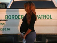 RIO GRANDE CITY, TX - DECEMBER 07: An immigrant from El Salvador, seven months pregnant, she said, stands next to a U.S. Border Patrol truck after turning herself in to border agents on December 7, 2015 near Rio Grande City, Texas. Many pregnant women, according to Border Patrol agents, cross …