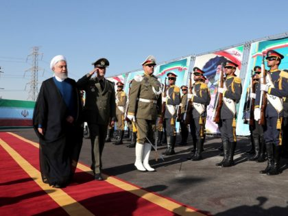 In this photo released by the official website of the office of the Iranian Presidency, President Hassan Rouhani, left, reviews an honor guard as he is accompanied by his Defense Minister Gen. Amir Hatami during a ceremony to unveil Iran-made Bavar-373 air-defense missile system, Iran, Thursday, Aug. 22, 2019. Iran …