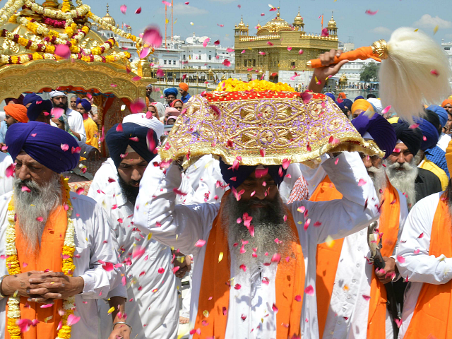 An Indian Sikh priest (R) carries the Sikh holy book during a procession from the Sri Akal Takhat at the Sikh Shrine to the Golden Temple in Amritsar on April 8, 2015 on the eve of the 394th birth anniversary of the ninth Sikh Guru, Teg Bahadur. Guru Tegh Bahadur, …
