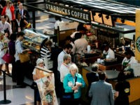 In this Thursday, May 30, 2013, file photo, customers line up at a Starbucks Coffee in New York. Starbucks wants a little extra change for that latte. The Seattle-based coffee company says it's hiking prices on average by 1 percent nationally starting on Tuesday, June 25, 2013, but it says …
