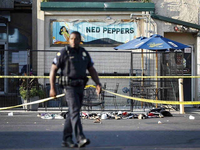 Shoes are piled outside the scene of a mass shooting including Ned Peppers bar, Sunday, Aug. 4, 2019, in Dayton, Ohio. Several people in Ohio have been killed in the second mass shooting in the U.S. in less than 24 hours, and the suspected shooter is also deceased, police said. …