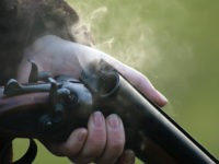Smoke rises from the barrels of a shotgun.