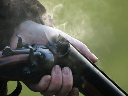 Smoke rises from the barrels of a shotgun.