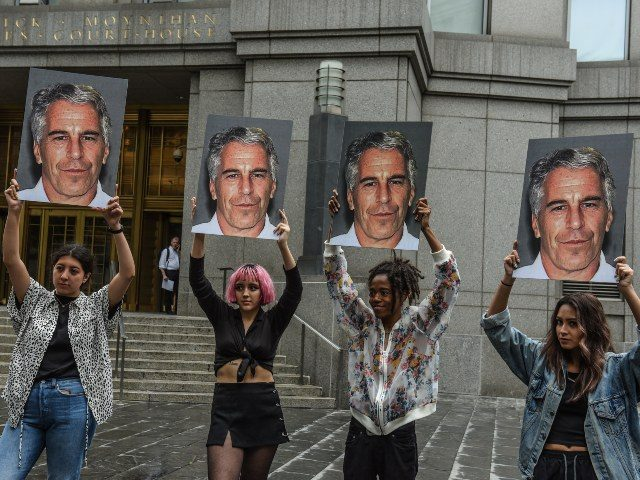 women holding pictures of Jeffrey Epstein
