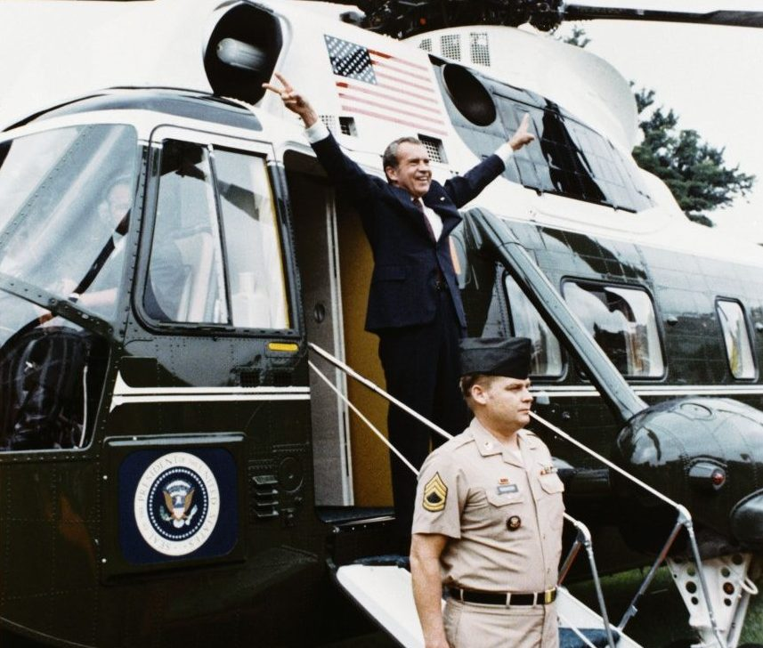 "President Nixon gives his famous ""V"" sign as he departs the White House for the last time"