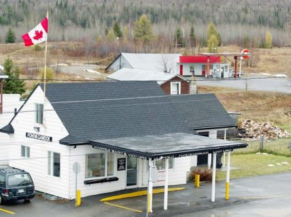 Ouellete's Gaz Bar, background, sits in Estcourt Station, Maine, 150 feet from the U.S. border with Canada at the town of Pohenegamook, Quebec, Monday, Nov. 11, 2002. The gas station is only accessible by car from Canada, and is in view of the Canadian Customs office, foreground. Michel Jalbert, of …