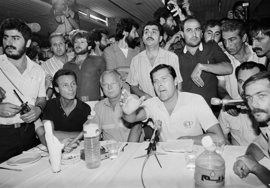Hostage Allyn Conwell, 39, of Houston, Texas, waves his hand and yells as he replies to reporter's questions during a news conference at Beirut International Airport Thursday, June 20, 1985. Journalists were pushed and shoved by Shiite Muslim AMAL Militiamen away from the five hostages. The Americans are part of 40 hostages taken during highjacking of TWA flight 847. Sitting to Conwell's right is Peter Hill, 57, of Hoffman Estates, Ill., Thomas Cullins, 42, Burlington, Vt. At his left is Arthur Toga, 33, of St. Louis, Mo. (AP Photo/Azakir)