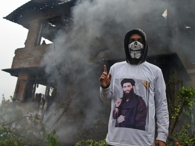 A Kashmiri protestor wears a shirt depicting a picture of a militant commander Zakir Musa as he stands in front of a damaged house following a gun battle between a top militant commander Zakir Musa of Ansar Ghazwat-ul-Hind group and Indian government forces at Dadsar village in Tral, south of …