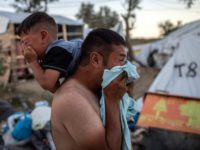 OPSHOT - A man and a boy react cry after police fired tear gas during clashes outside the refugee camp of Moria on the Greek island of Lesbos, on September 29, 2019. - At least two migrants died on September 29 in a fire at a Greek island refugee camp, …