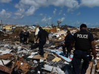 Members of the police join a recovery team looking in the debris in Marsh Harbour, Bahamas, on September 10, 2019, one week after Hurricane Dorian. - Bahamas authorities have updated the death toll from Hurricane Dorian to 50 with the number expected to climb, local media reported, as thousands are …